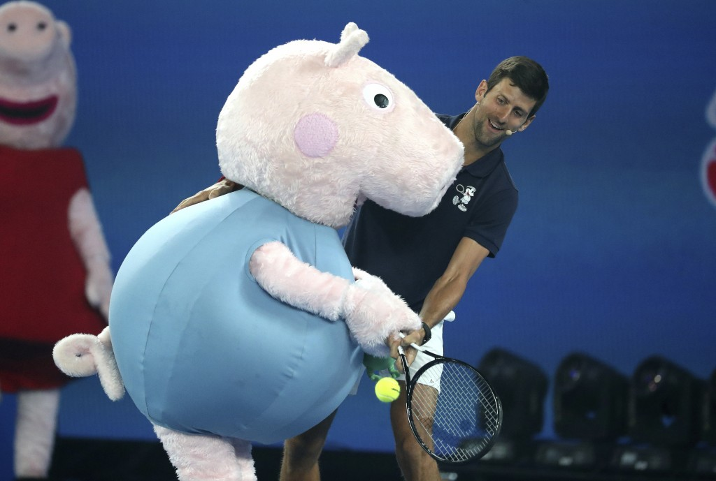 Serbia's Novak Djokovic and Peppa Pig combine to return a shot during Kids Tennis Day ahead of the Australian Open tennis championships in Melbourne,