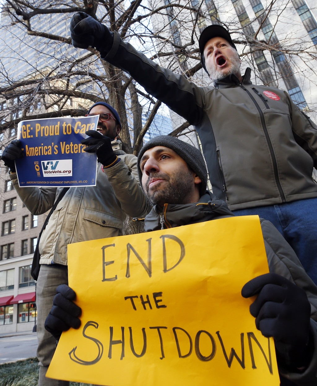 Government workers and their supporters hold signs during a protest in Boston, Friday, Jan.11, 2019. The workers rallied with Democratic U.S. Sen. Ed