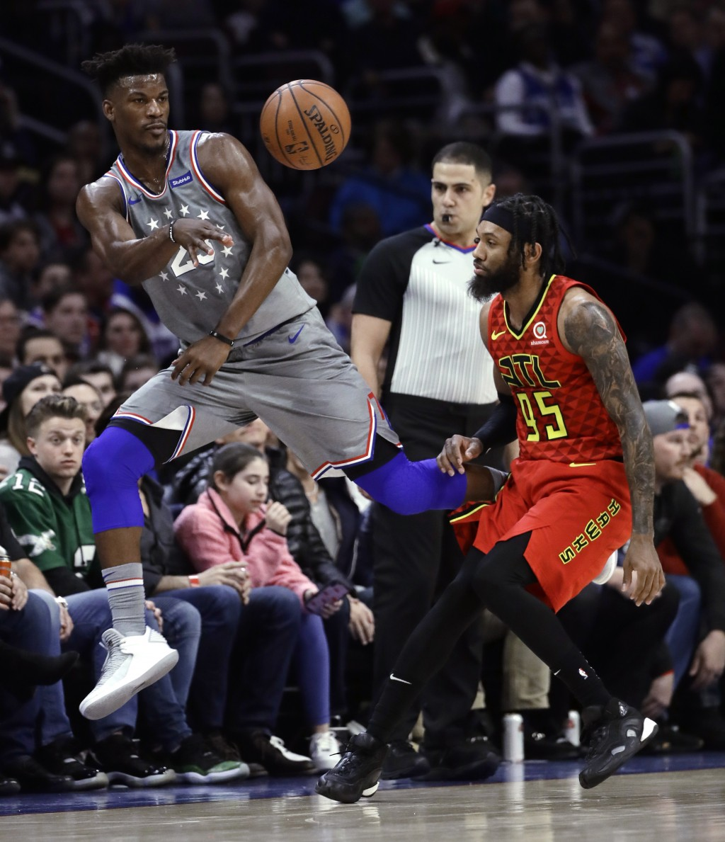 Philadelphia 76ers' Jimmy Butler, left, passes the ball as Atlanta Hawks' DeAndre' Bembry defends during the first half of an NBA basketball game Frid