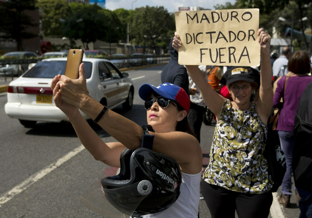 """An opposition member take a selfie beside to a woman holding up a sign that reads in Spanish """" Maduro dictator out"""" during a protest in Caracas, Venez..."""