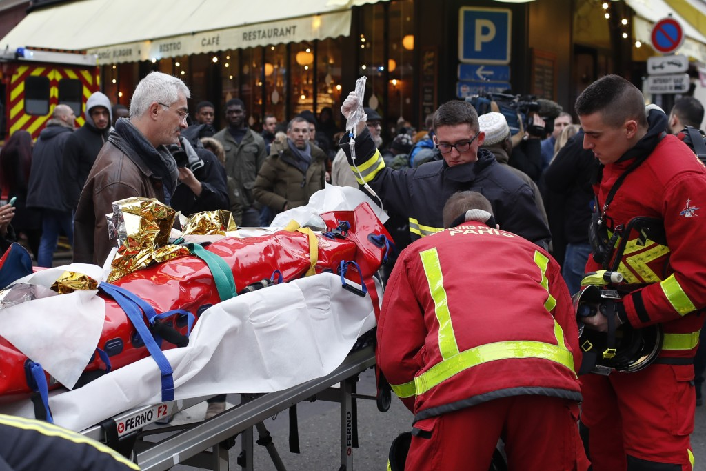 Firefighters tend to a wounded person near the scene of a gas leak explosion in Paris, France, Saturday, Jan. 12, 2019. Paris police say several peopl