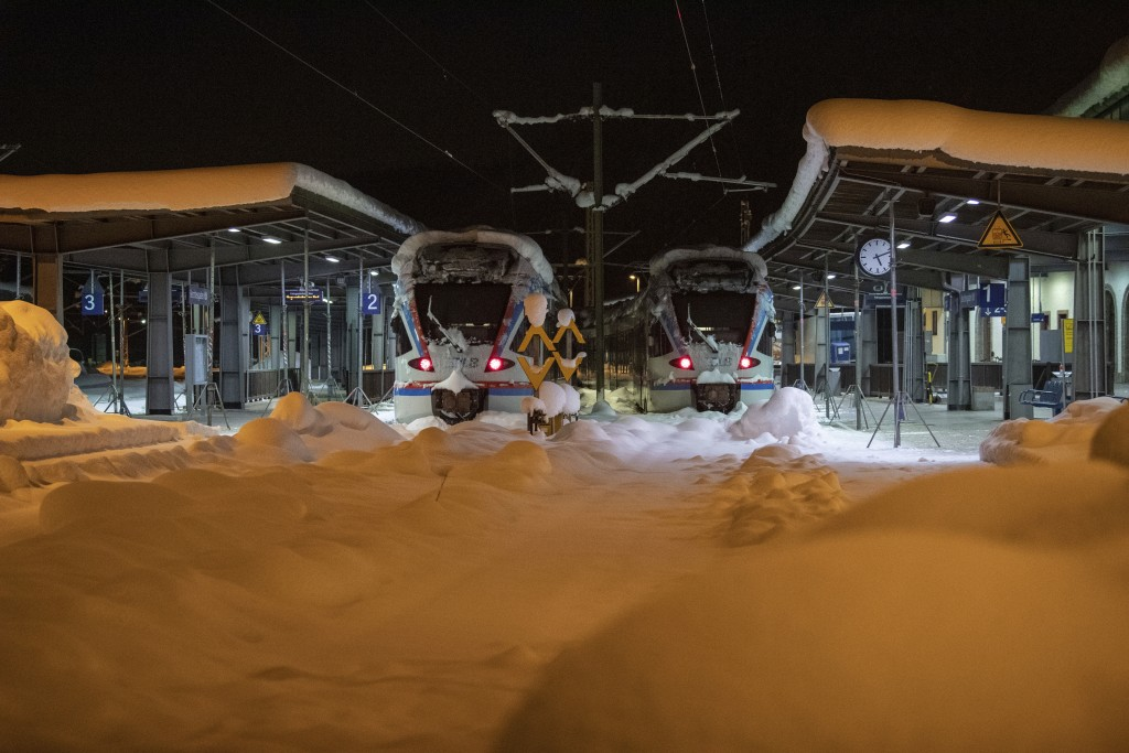 Two trains stand in a snowed-in railway station in the Bavarian city Berchtesgaden, Germany, Saturday, Jan. 12, 2019. (Lino Mirgeler/dpa via AP)