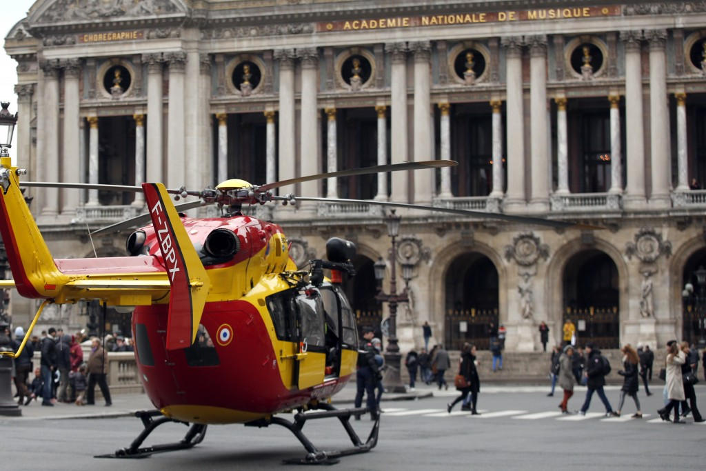 A rescue helicopter stands ready to evacuate wounded people in front of the Paris Opera House following a gas leak explosion, France, Saturday, Jan. 1