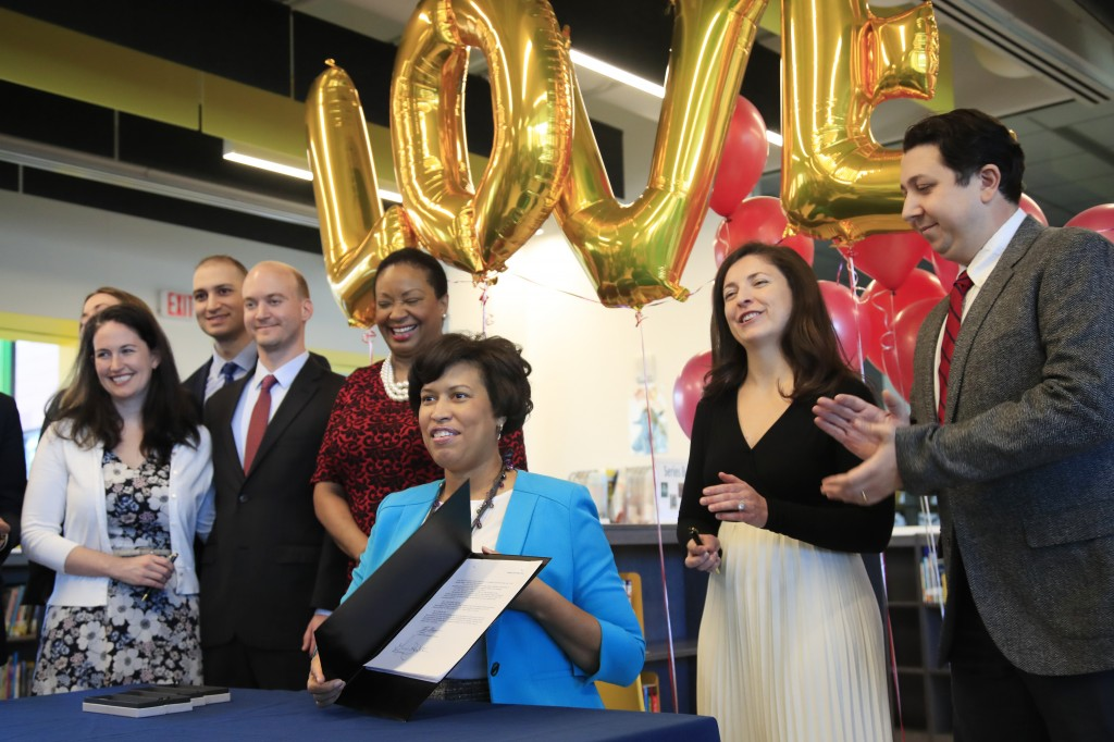 In this Jan. 11, 2019, photo, District of Columbia Mayor Muriel Bowser, seated, holds the LOVE Act she signed, joined by soon to be newlyweds, Claire