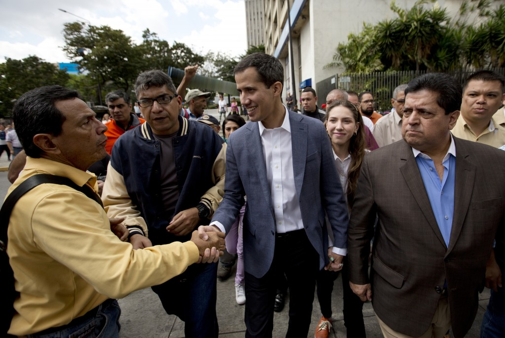 Juan Guaido, center, President of the Venezuelan National Assembly greets supporters upon his arrival to attend a public session with members of the o...