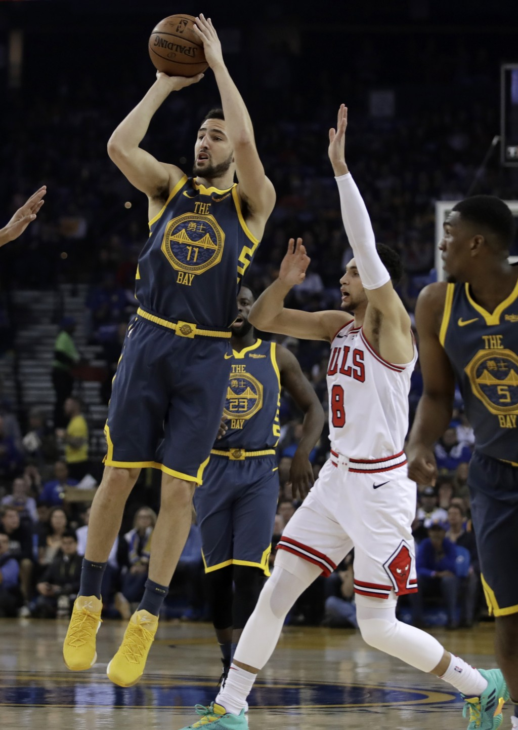 Golden State Warriors' Klay Thompson, left, shoots past Chicago Bulls' Zach LaVine (8) during the first half of an NBA basketball game Friday, Jan. 11
