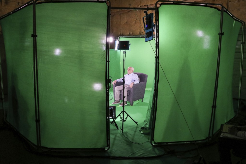 This August 2018 photo shows Holocaust survivor Max Glauben sitting in an interactive green screen room while filming a piece for the Dallas Holocaust
