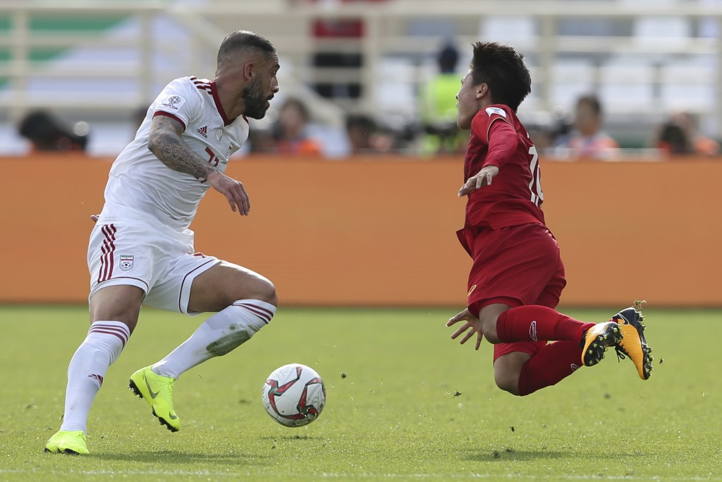 Vietnam's midfielder Nguyen Quang Hai, right, is fouled by Iran's midfielder Ashkan Dejagah during the AFC Asian Cup group D soccer match between Iran