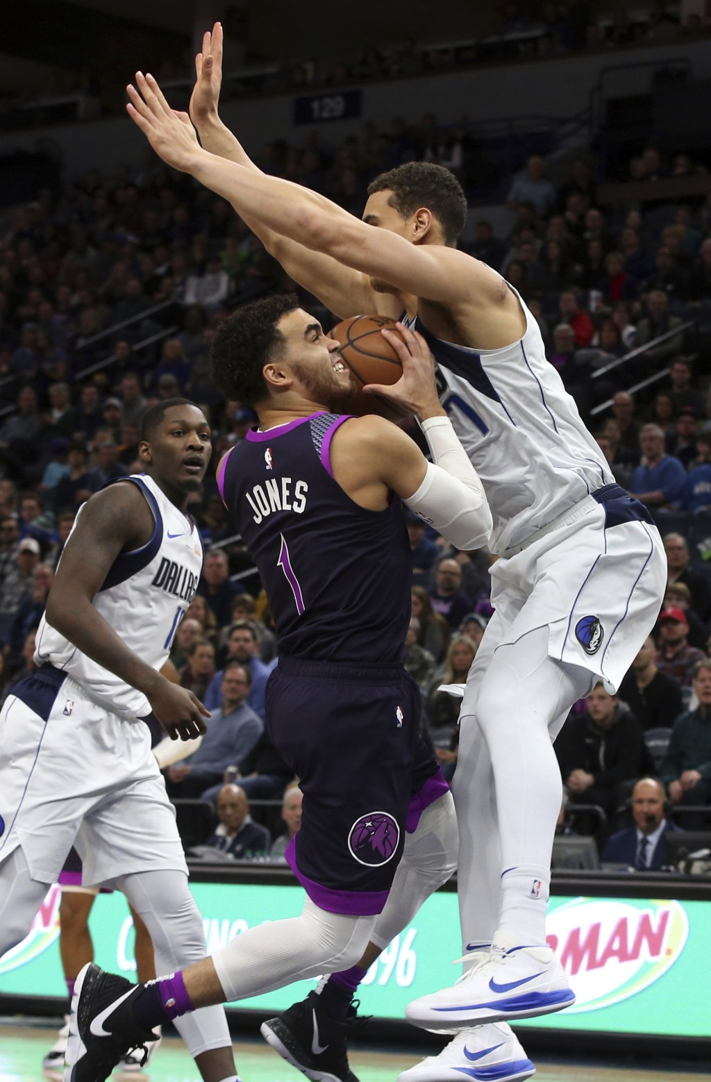 Minnesota Timberwolves' Tyus Jones, left, eyes the basket as Dallas Mavericks' Luka Doncic, of Slovenia, hovers over him in the first half of an NBA b
