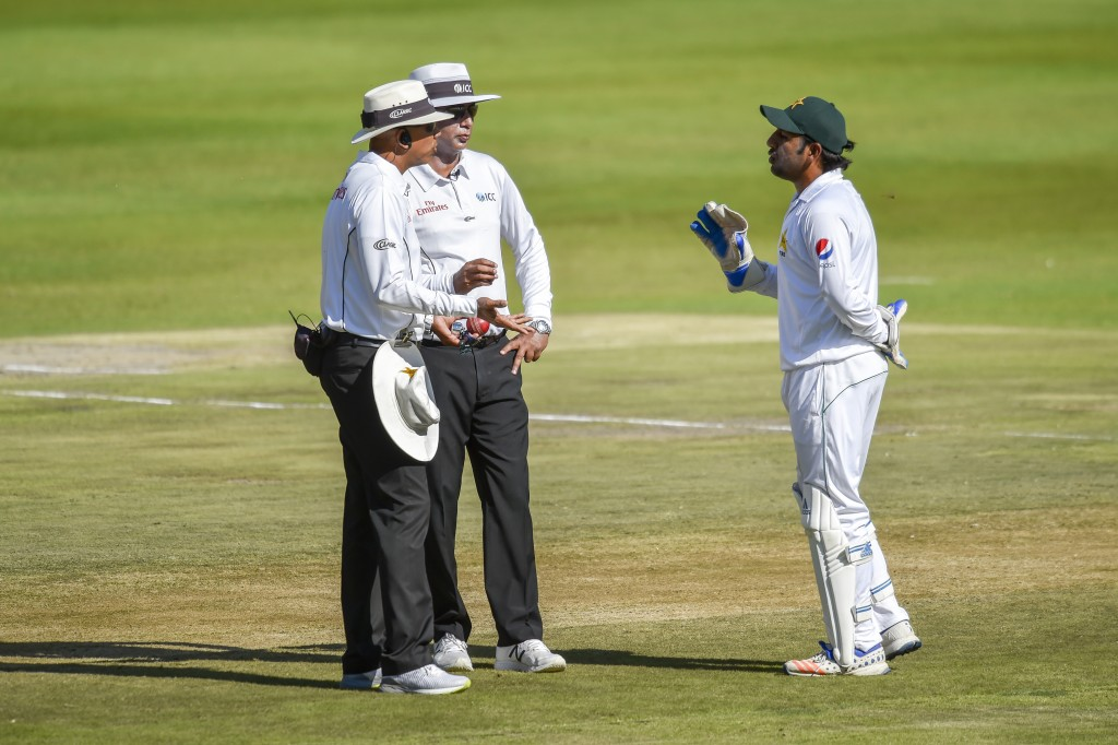 Pakistan's Wicketkeeper and captain Sarfraz Ahmed talks to the Umpires on day one of the third cricket test match between South Africa and Pakistan at...