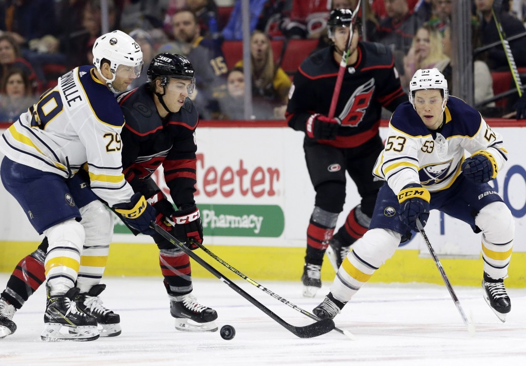 Buffalo Sabres' Jason Pominville (29) reaches for the puck with Carolina Hurricanes' Teuvo Teravainen, of Finland, and Sabres' Jeff Skinner (53) durin