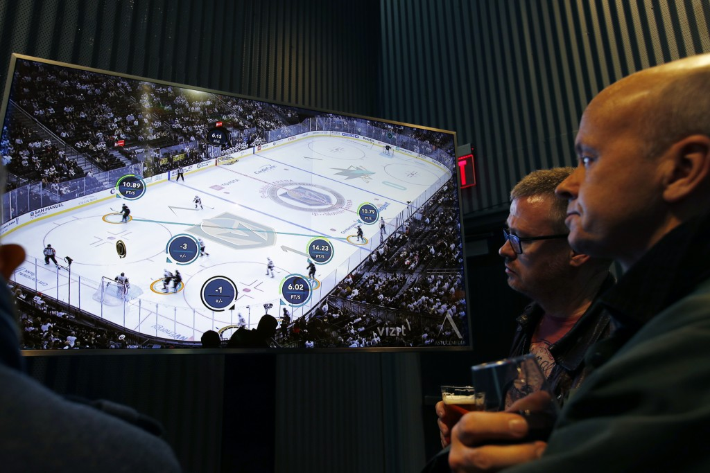 People watch real-time puck and player tracking technology on display during an NHL hockey game between the Vegas Golden Knights and the San Jose Shar...