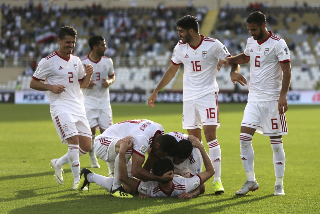 Iran's forward Sardar Azmoun, center bottom, celebrates with his teammates scoring his side's second goal during the AFC Asian Cup group D soccer matc