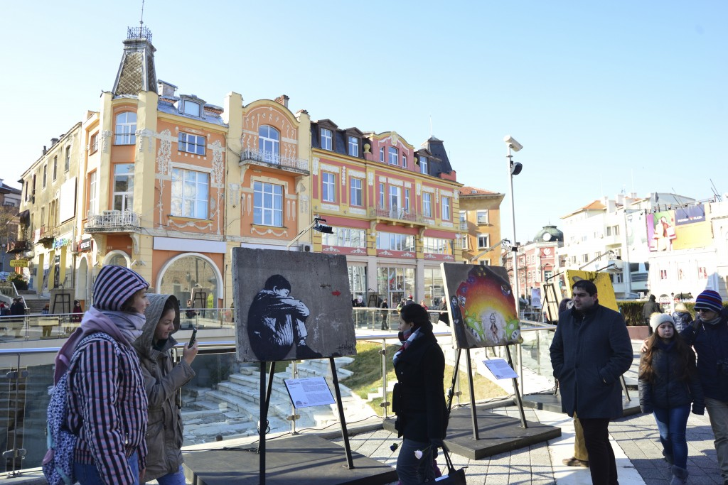 People walk past works part exhibits of the Art Liberte exhibition, the first traveling exhibition celebrating the 30 years anniversary of fall of the
