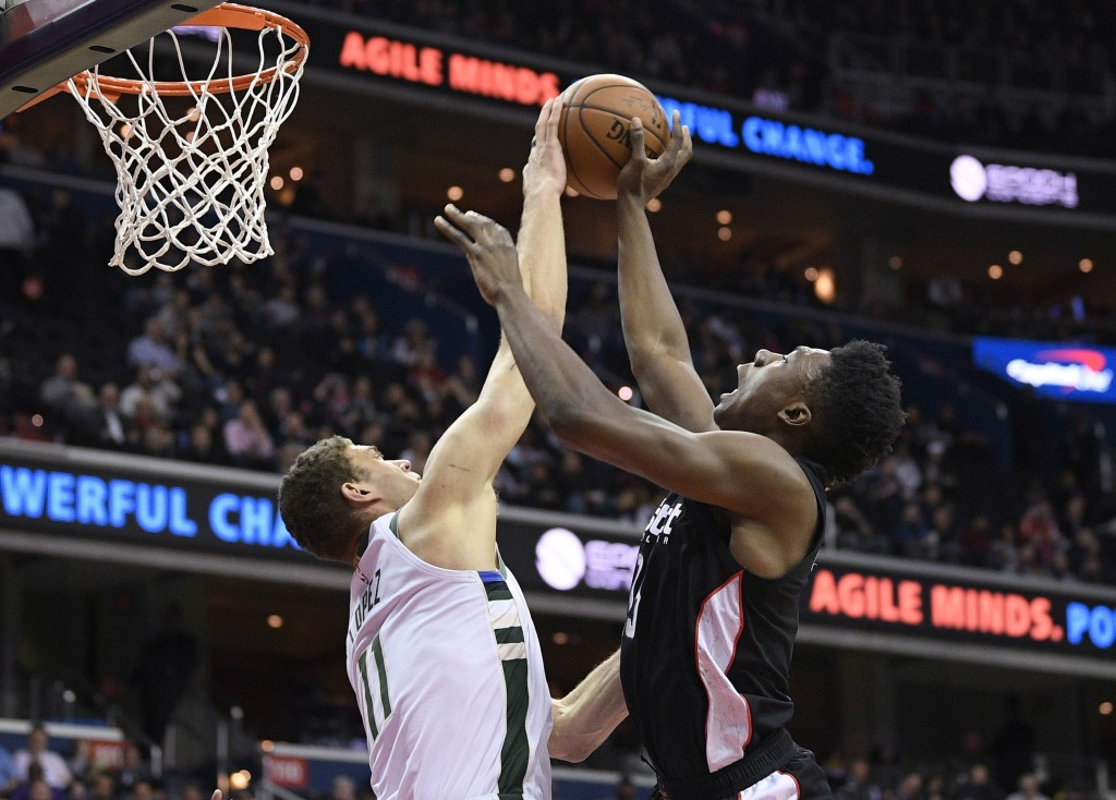Milwaukee Bucks center Brook Lopez (11) blocks a shot by Washington Wizards center Thomas Bryant (13) during the first half of an NBA basketball game