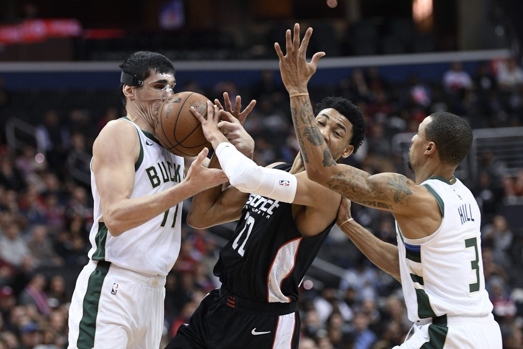 Milwaukee Bucks forward Ersan Ilyasova, left, and guard George Hill (3) battle for the ball against Washington Wizards forward Otto Porter Jr. (22) du
