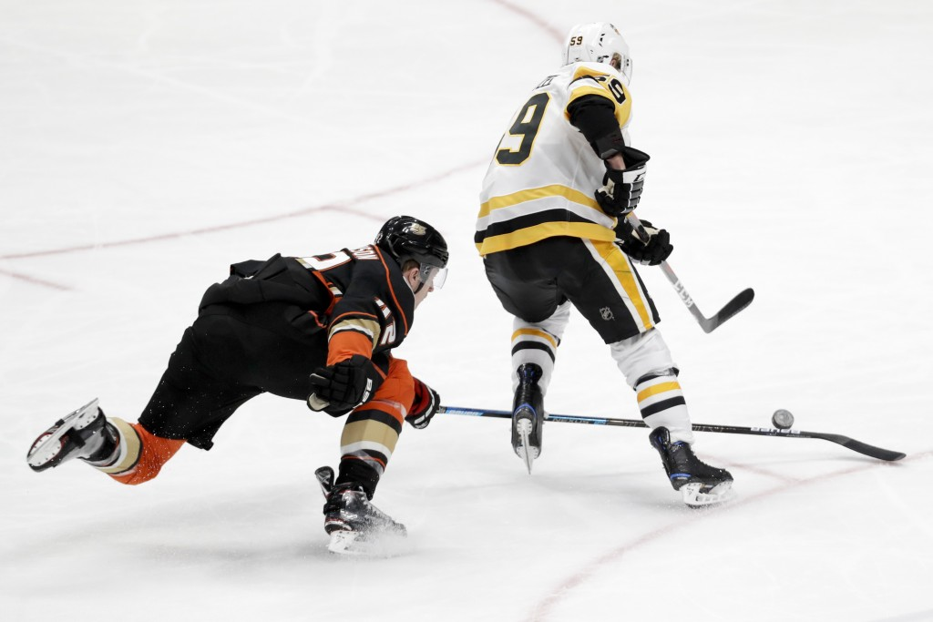 Anaheim Ducks defenseman Josh Manson, left, trips Pittsburgh Penguins left wing Jake Guentzel during the second period of an NHL hockey game in Anahei
