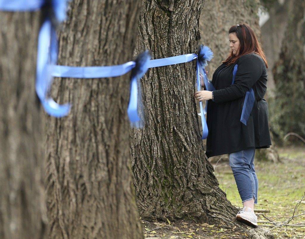 Vicky Oliverius ties blue ribbons on trees, Friday, Jan. 11, 2019, near the scene were Davis Police Officer Natalie Corona was shot and killed in Davi