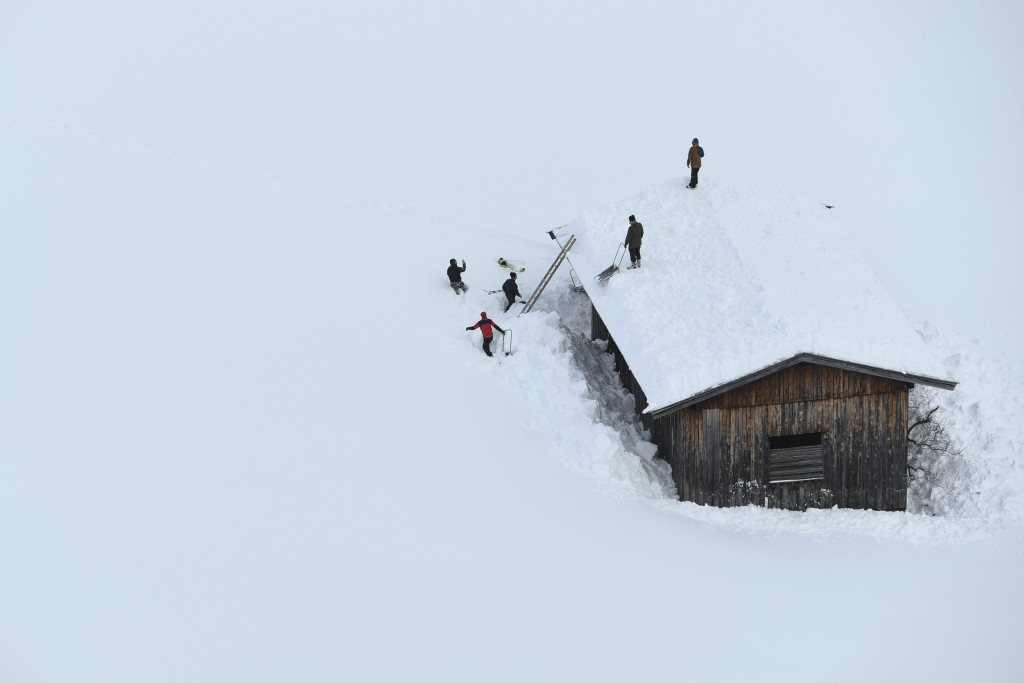 Men clean a roof from snow  in Lofer, Austrian province of Salzburg on Friday, Jan. 11, 2019.(AP Photo/Kerstin Joensson)