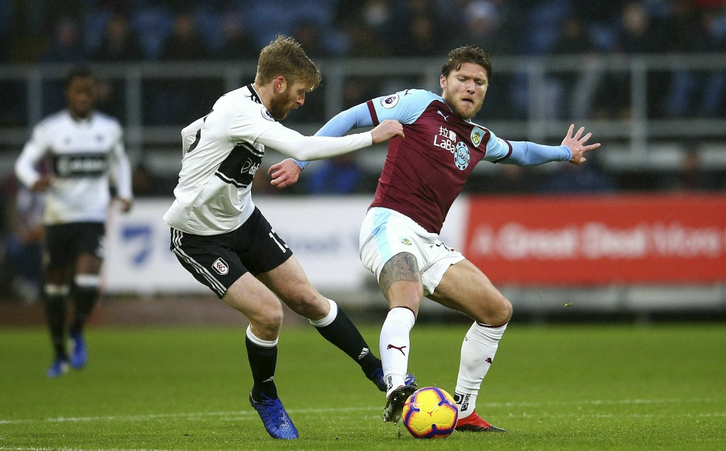Fulham's Tim Ream, left, and Burnley's Jeff Hendrick battle for the ball during the English Premier League soccer match between Burnley F.C and Fulham
