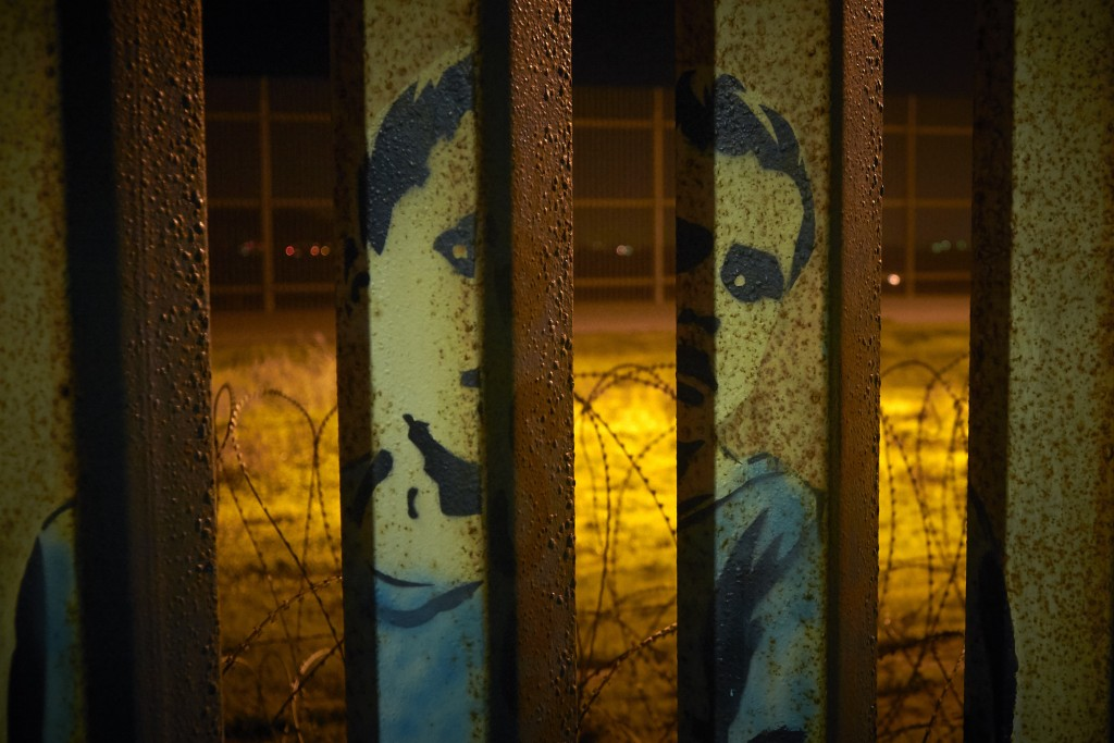 An image of a boy is painted on the bars of the border wall, in front of coils of razor wire Friday, Jan. 11, 2019, seen from Tijuana, Mexico. The par