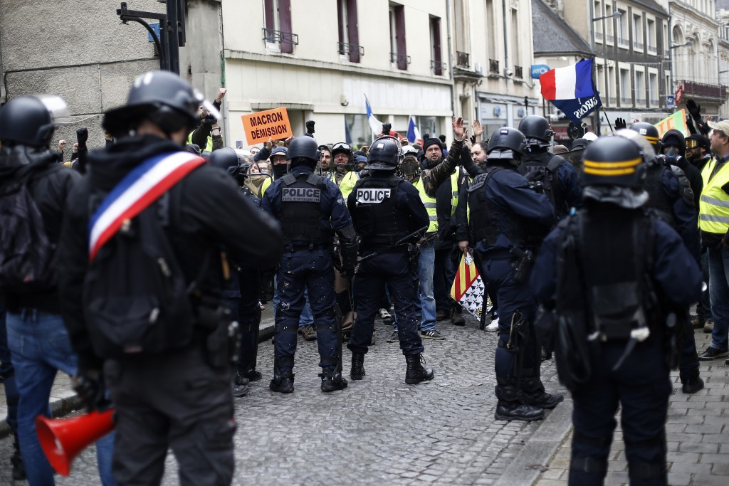 French police, one wearing a ribbon in the colors of the French flag, block a demonstration of yellow vest protestors in Bourges, central France, Satu