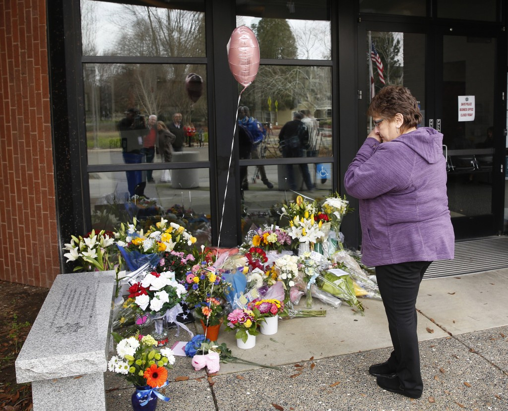 Mary Ann Doerzbacher wipes her eyes after placing flowers on a memorial outside the Davis Police Department for slain Davis Police Officer Natalie Cor
