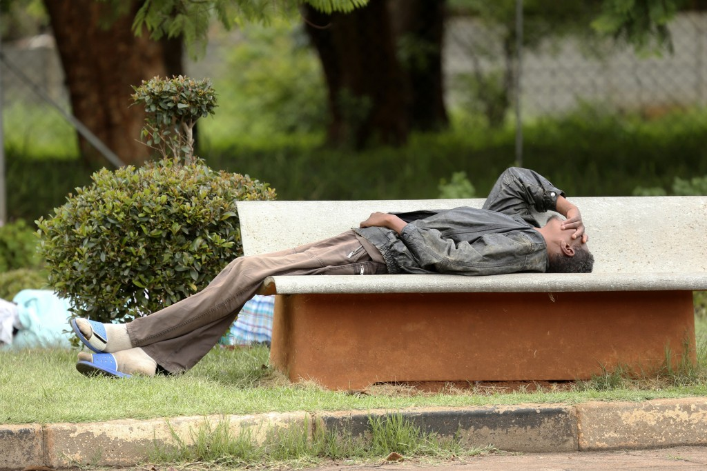 In this Jan. 9, 2019, photo, a man lies on a bench outside a government hospital after being turned away during the doctors strike at Parirenyatwa Hos