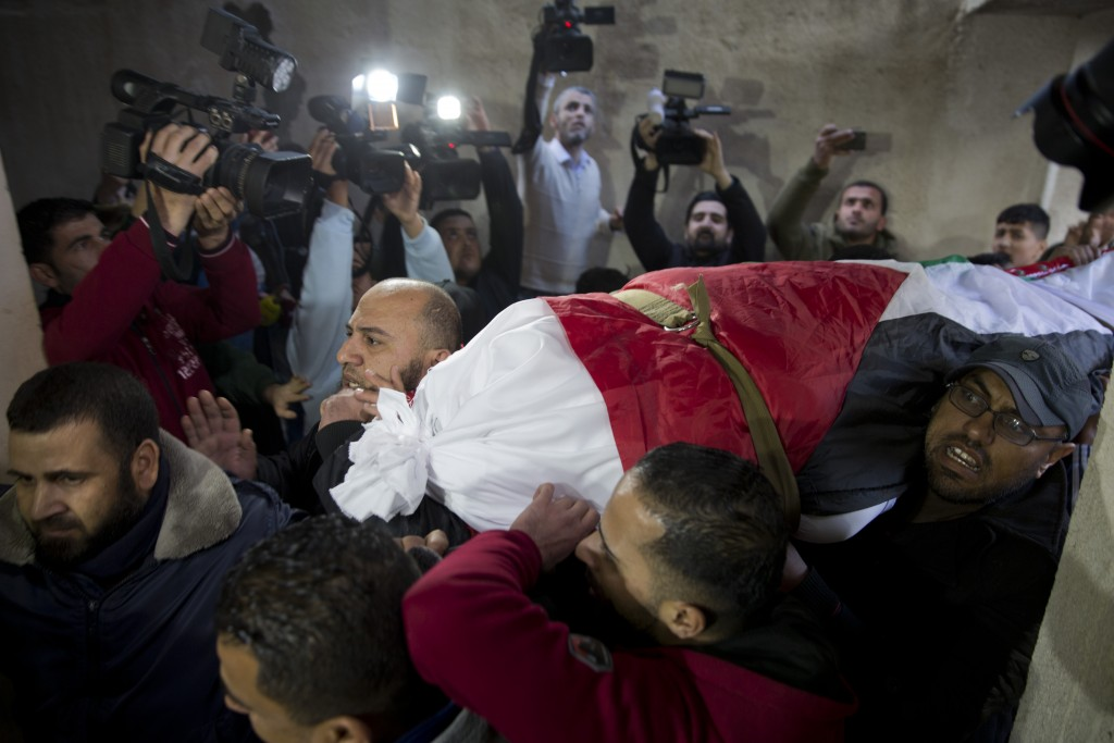 Mourners carry the body of Palestinian woman, Amal al-Taramsi, 43, who was killed by Israeli troops during Friday's protest at the Gaza Strip's border
