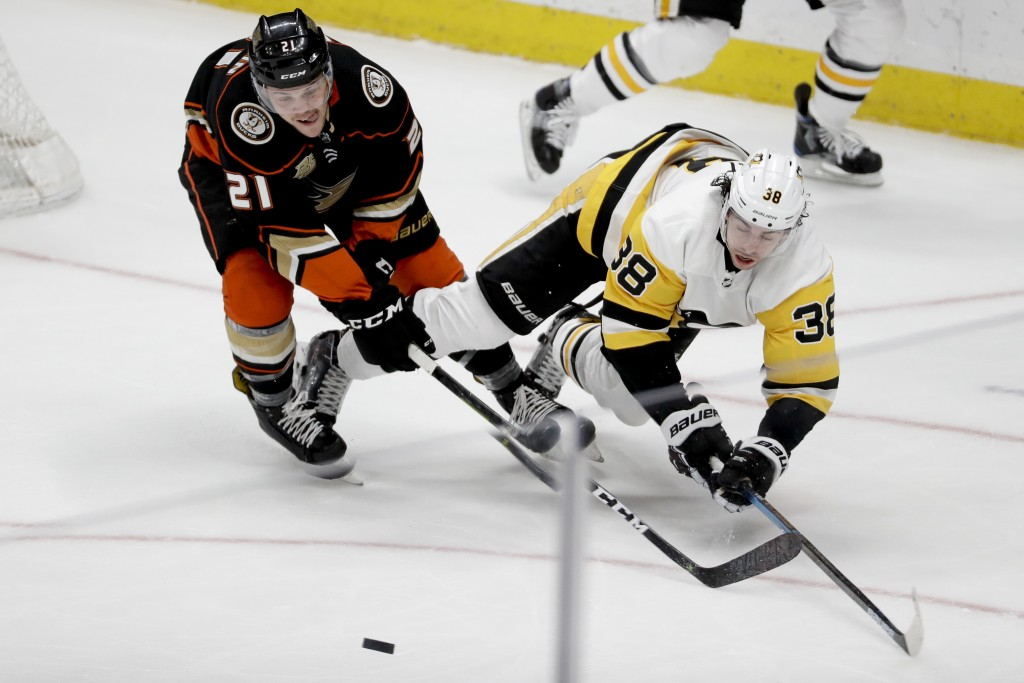 Anaheim Ducks defenseman Jake Dotchin, left, vies for the puck with Pittsburgh Penguins center Derek Grant during the second period of an NHL hockey g