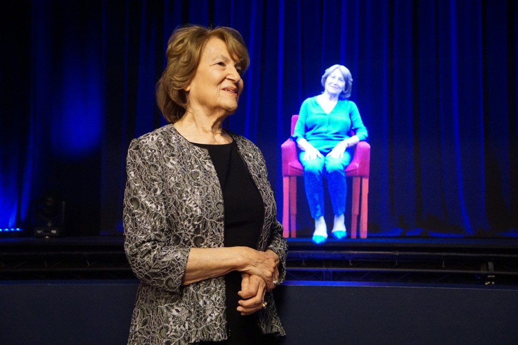 In this October 2017 photo, Holocaust survivor Fritzie Fritzshall stands in front of a hologram of herself at The Abe & Ida Cooper Survivor Stories Ex