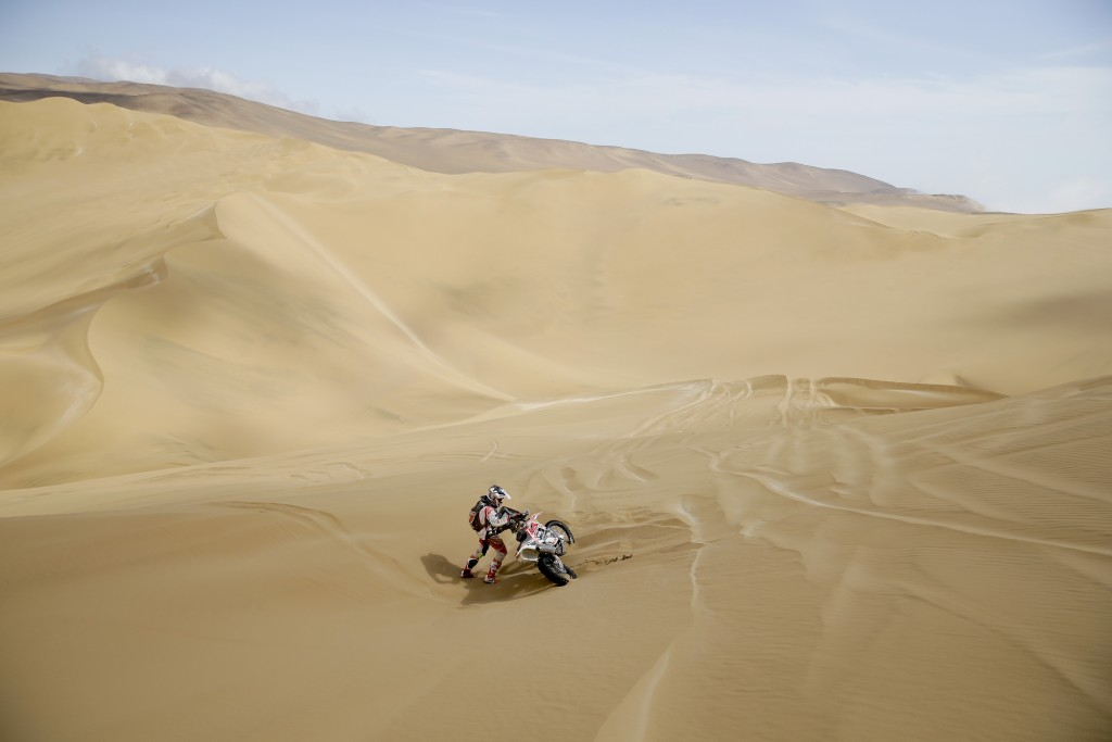 Marcel Snijders of Netherlands lifts his KTM after falling during the stage five of the Dakar Rally between Tacna and Arequipa, Peru, Friday, Jan. 11,