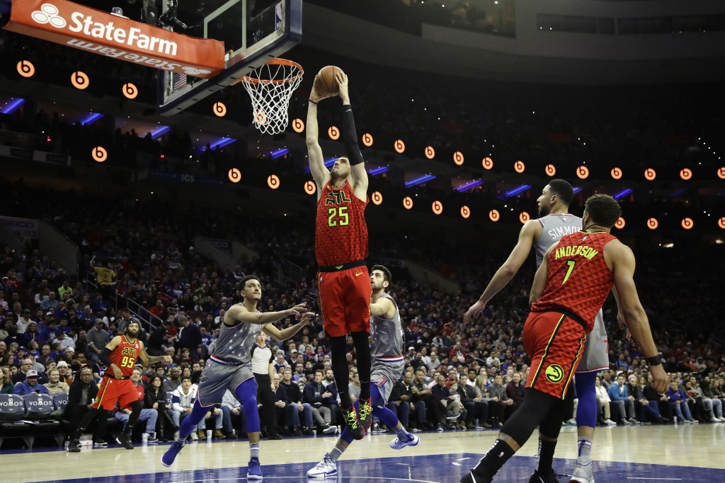 Atlanta Hawks' Alex Len (25) goes up for a dunk past Philadelphia 76ers' Landry Shamet (1) and Furkan Korkmaz (30) during the first half of an NBA bas