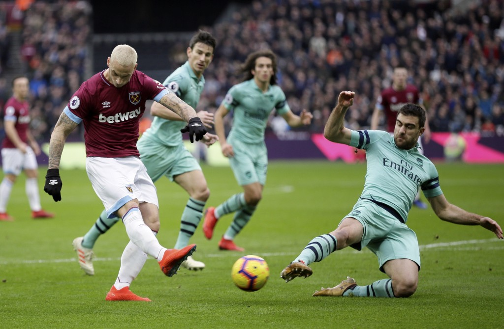 Arsenal's Sokratis Papastathopoulos, right, blocks a shot from West Ham's Marko Arnautovic during the English Premier League soccer match between West