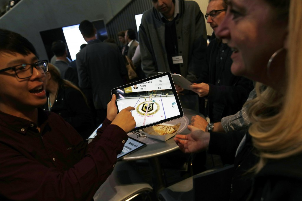 People watch real-time puck and player tracking technology on a tablet during an NHL hockey game between the Vegas Golden Knights and the San Jose Sha...