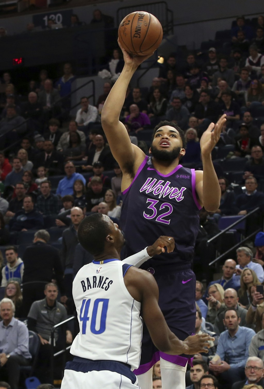 Minnesota Timberwolves' Karl-Anthony Towns, top, shoots over Dallas Mavericks' Harrison Barnes in the first half of an NBA basketball game Friday, Jan