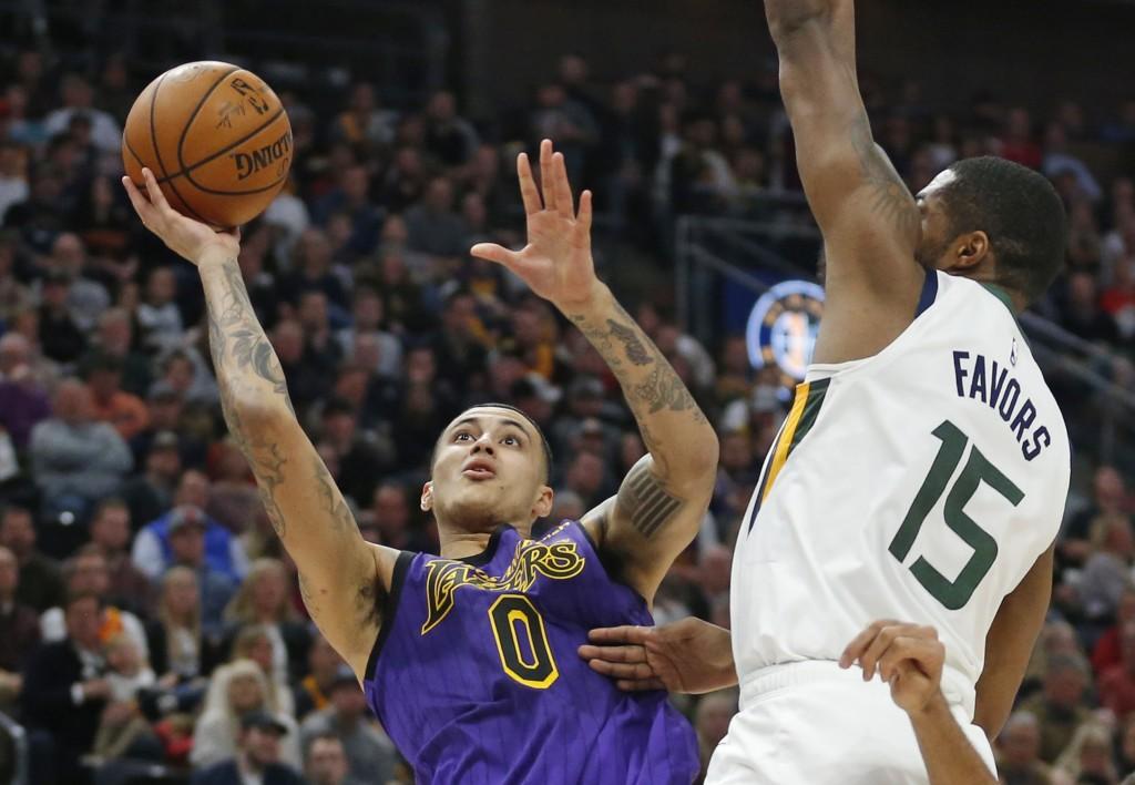 Los Angeles Lakers forward Kyle Kuzma (0) shoots as Utah Jazz forward Derrick Favors (15) defends during the first half of an NBA basketball game Frid