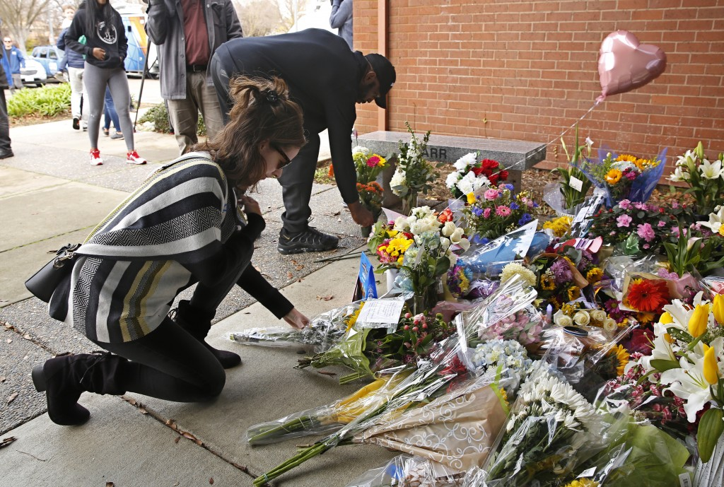 Mourners place flowers on a memorial outside the Davis Police Department for slain Davis Police Officer Natalie Corona, Friday, Jan. 11, 2019, in Davi