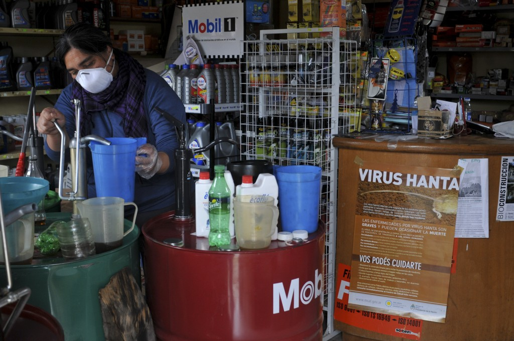 A woman works at her shop in Epuyen, Argentina, Friday, Jan. 11, 2019. An Argentine judge has ordered 85 residents of a remote Patagonian town to stay