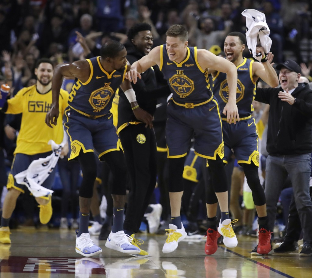Golden State Warriors' Jonas Jerebko (21) celebrates a score with Stephen Curry, right, and Kevin Durant (35) during the first half of the team's NBA
