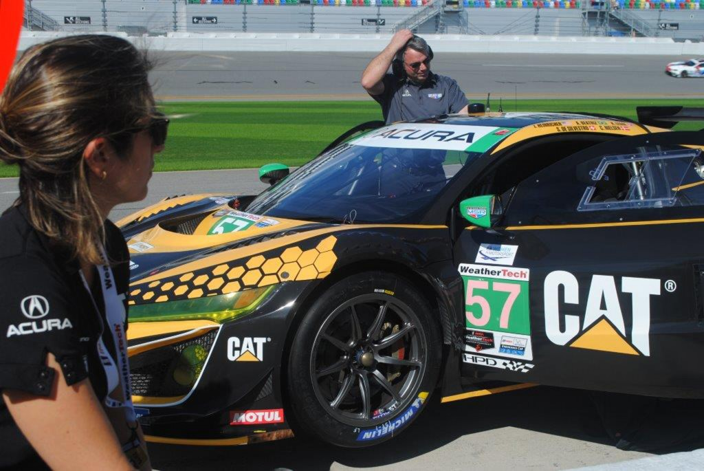 Bia Figueiredo of Brazil, left, watches crew members prepare the race car during a test session at Daytona International Speedway in Daytona Beach, Fl