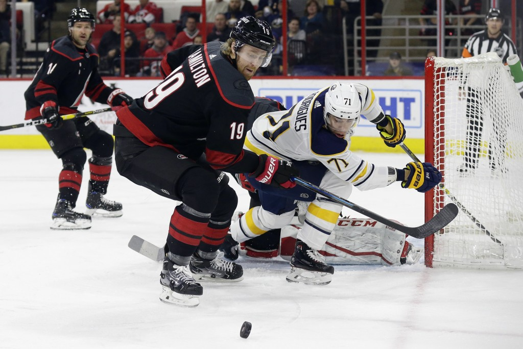 Carolina Hurricanes' Dougie Hamilton (19) and Buffalo Sabres' Evan Rodrigues (71) struggle for possession of the puck during the first period of an NH