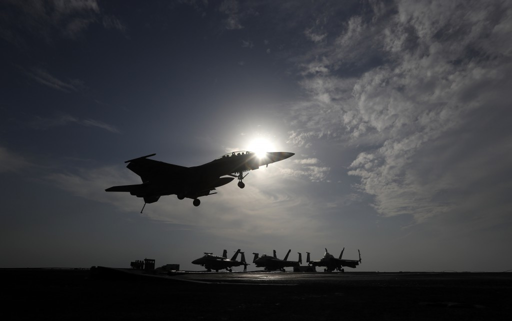 FILE - In this file picture taken on Monday, Nov. 21, 2016, a U.S. Navy fighter jet lands on the deck of the U.S.S. Dwight D. Eisenhower aircraft carr