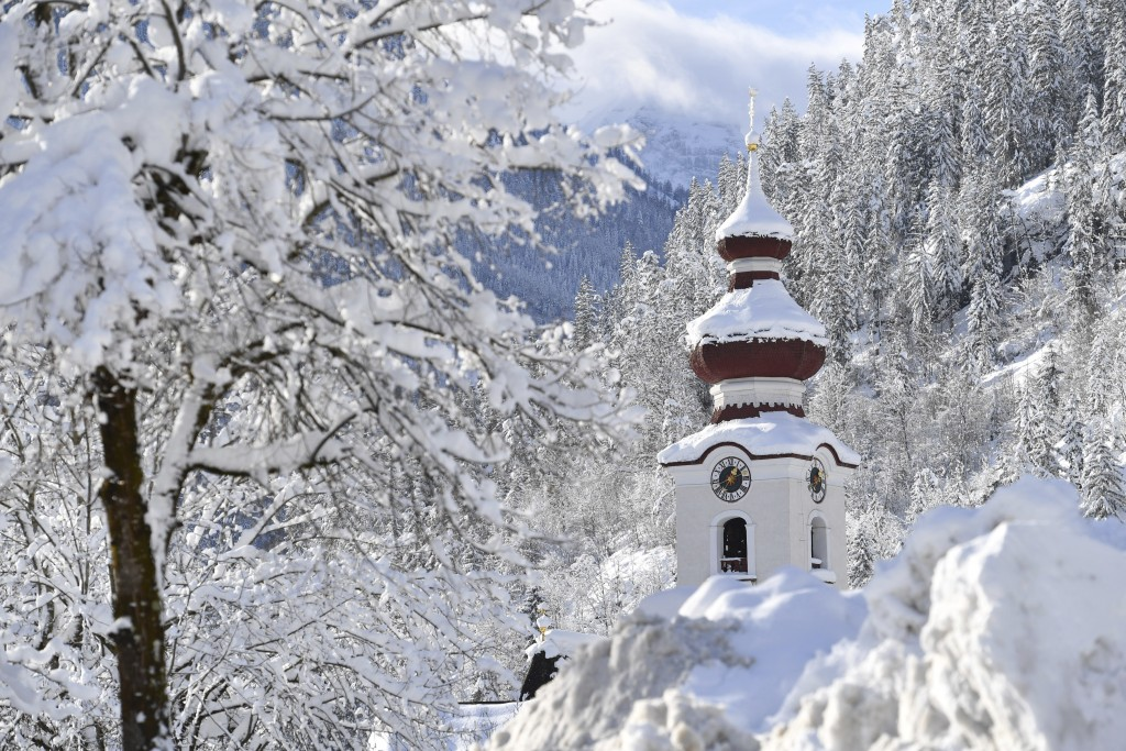 The steeple of the Loferer church is seen through the snow on Friday, Jan. 11, 2019 in Lofer, Austrian province of Salzburg.(AP Photo/Kerstin Joensson