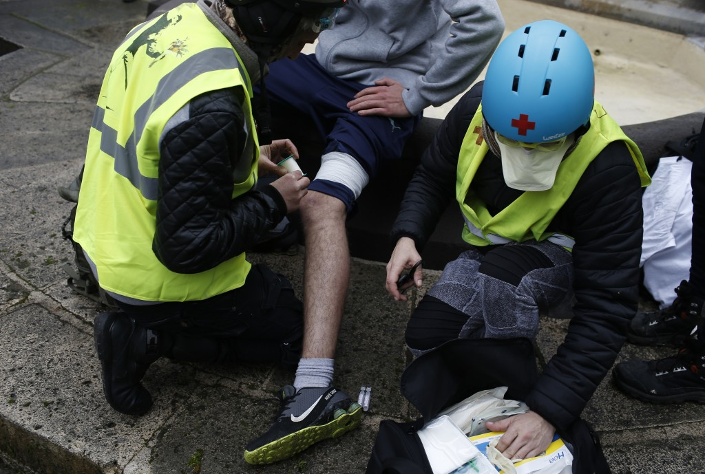 A protester hit by a flash-ball is treated during a yellow vest demonstration in Bourges, central France, Saturday, Jan. 12, 2019. Paris brought in ar