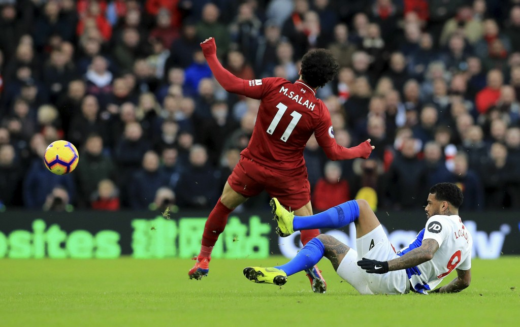 Liverpool's Mohamed Salah, left, and Brighton & Hove Albion's Jurgen Locadia battle for the ball during the English Premier League soccer match betwee