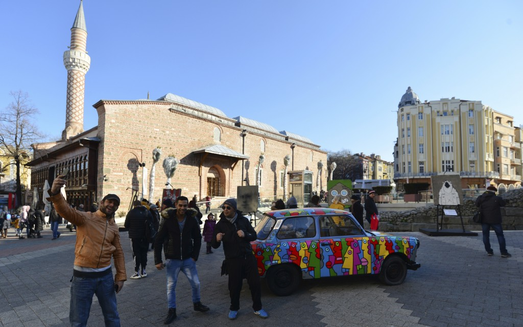 People take selfies with Trabant car exhibited as part of Art Liberte, the first traveling exhibition marking the occasion of the 30 years anniversary