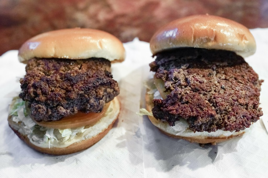 """A conventional beef burger, left, is seen Friday, Jan. 11, 2019, next to """"The Impossible Burger"""", right, a plant-based burger containing wheat protein"""