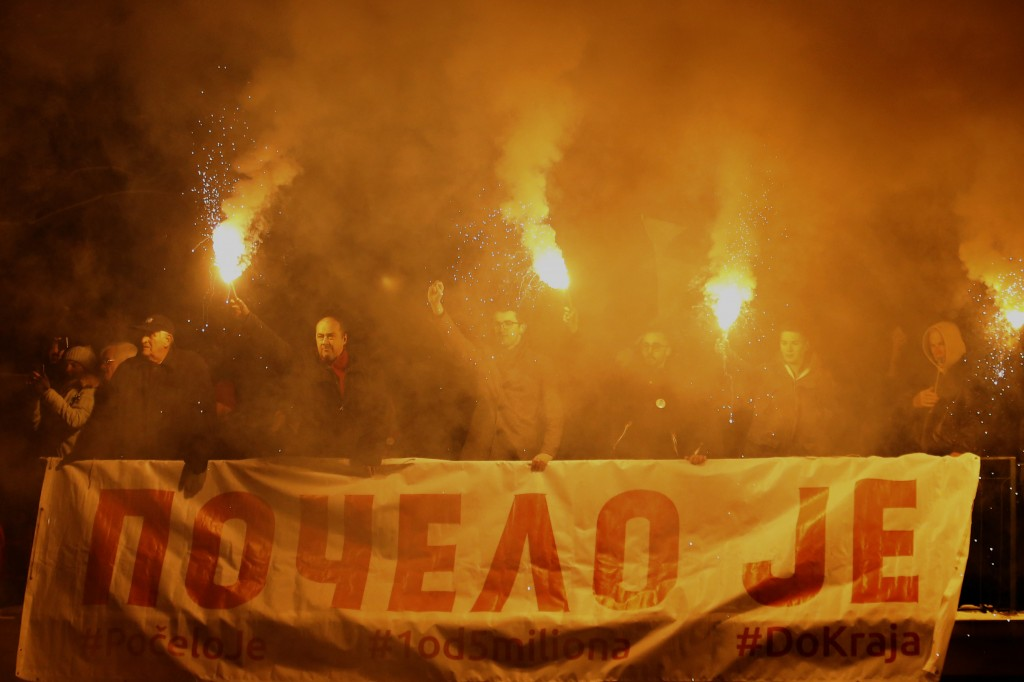 """People light torches and hold a banner that reads """"It has Started"""" during a protest against populist President Aleksandar Vucic in Belgrade, Serbia, S"""