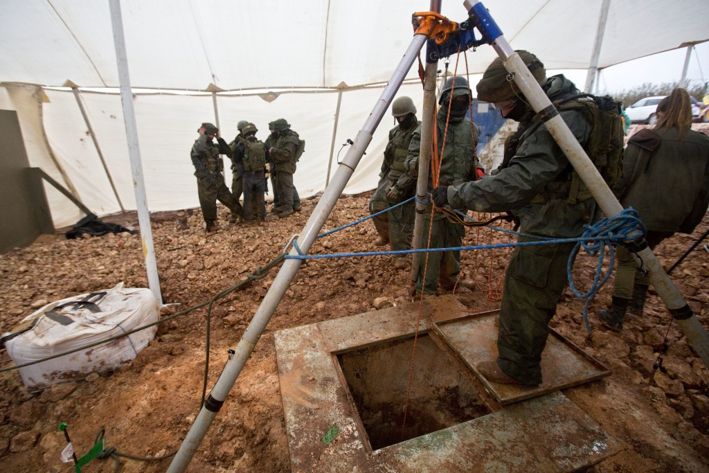 File - In this Wednesday, Dec. 19, 2018 file photo, Israeli soldiers stand around the opening of a hole that leads to a tunnel that the army says cros